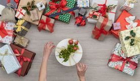 Hands with gift present box in vertical top view wooden table full of christmas or birthday gifts presents.Xmas winter. Holiday season party social media card royalty free stock photos