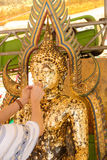 Hands gilding gold leaf onto the Buddha statue image.Which peopl. Hands gilding gold leaf onto the Buddha statue image Royalty Free Stock Photos
