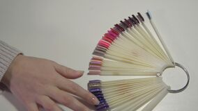 Hands of a girl in a beauty salon chooses the future manicure in a color palette. Hands of a girl in a beauty salon chooses the future manicure in a color stock video footage