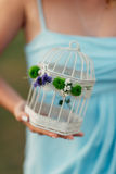 In the hands of a girl a cage for a bird Stock Photo