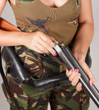 Hands girl charging a gun. Gray background. close-up. Royalty Free Stock Images