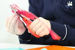 Hands of girl cutting flower from red paper for crafts. Close up royalty free stock image