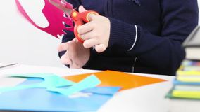 Hands of girl cutting shape from colored paper for crafts stock video