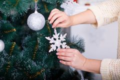 The girl`s hands decorate the Christmas green tree. Hands of a girl decorate a Christmas green tree with a white paper snowflake Royalty Free Stock Photo