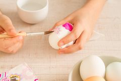 The hands of a girl decorating easter egg. The hands of a girl preparing and decorating easter eggs with a papper napkin, close up stock images
