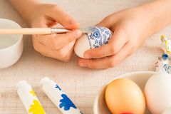 The hands of a girl decorating easter egg. The hands of a girl preparing and decorating easter eggs, close up royalty free stock photo