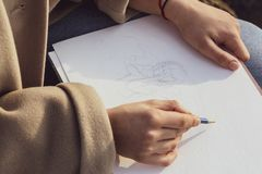 Hands of a girl while drawing a cartoon. Hands of a girl when drawing with pencil on the paper stock photography