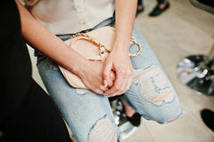 Hands of girl with handbag on ripped jeans at beauty salon. Morn Royalty Free Stock Photo