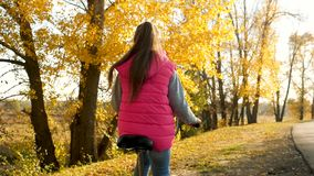 Hands of girl hold curved bicycle handlebar. girl riding bike and smiling in the autumn park. close-up stock video footage