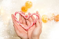 Hands holding a heart made of a christmas candy stock images