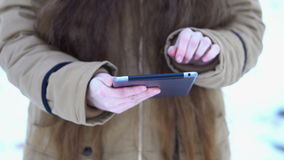 The hands of a girl with long hair holding a tablet, she reviews photos stock footage