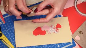 Scrap Valentine greeting card. Hands of girl making scrap Valentine greeting card stock video footage