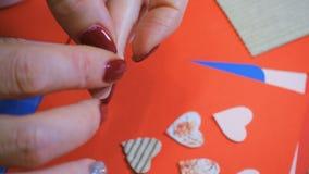 Girl making scrap Valentine greeting card. Hands of girl making scrap Valentine greeting card stock video footage