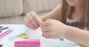 Hands of girl making shape using plasticine. Little girl molding shapes from colorful plasticine at home stock video footage