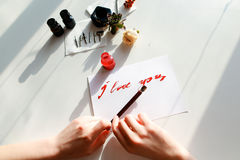 Hands of girl painter writes love text to postcard with with fou Royalty Free Stock Photography