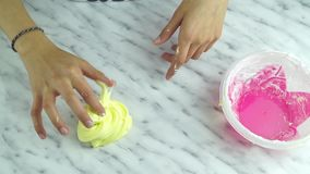 Hands of girl playing with slime. Close up on hands of girl playing with slime stock footage