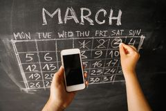 Hands of a girl with a smartphone on the background of the calendar written on the wall of a dark chalkboard. March month and Saturday royalty free stock image