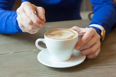 Hands of the girl stirring coffee behind a little table Royalty Free Stock Images