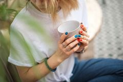 The hands of the girl touch the handmade jewelry. Girl and a cup. Handmade woman decorating stones closeup, meditation, morning, t royalty free stock images