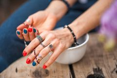 The hands of the girl touch the handmade jewelry. Girl and jewelry. Handmade woman decorating stones close up stock image