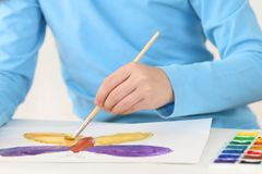 Hands of girl watercolor painting butterfly on table Stock Photos