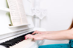 Hands girl who plays the piano. Selective focus. Royalty Free Stock Photography