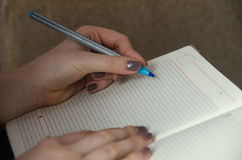 Hands of a girl who writes in a notebook royalty free stock image