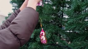 Hands girls decorate artificial Christmas tree outdoor. HD stock video