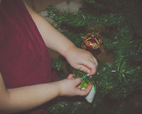 Hands girls decorate the Christmas tree close-up Stock Photos