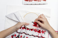 Hands girls embroider pattern using the frame. Woman embroiders national pattern red thread on a towel Royalty Free Stock Photo
