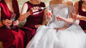 Hands of girls with glasses of champagne celebrating a wedding party. In a white wedding dress and red bridesmaids dresses Stock Photography