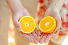 Hands girls and a guy with oranges Stock Photography