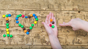 Hands girls laid out colored candies on the table. Stock Image