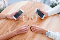 Hands of girls sitting at a table in a cafe, holding smart phones and drinking champagne. Stock Photo