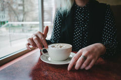 Hands girls take a cup of coffee with marshmallows in a cozy cafe. Hot drink for breakfast Royalty Free Stock Images