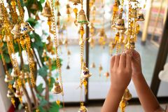 The hands of the girls are bracing gold. The hands of the girls are tied to the gold bells of the Buddhist faith. Thai beliefs, if written on the letter bells Stock Image