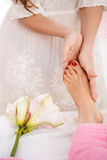 Hands giving foot massage working in bright and pleasing salon. Closeup of female hands giving foot massage to lady after pedicure. Health and beauty concept Stock Photo