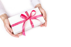 hands giving gift box with pink ribbon on white background Stock Images