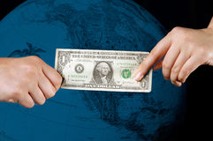 Hands giving money or buying. This stock photo shows one hand taking a dollar from someone.  A blue tinted globe is faintly visible in the background.  Can Royalty Free Stock Photos