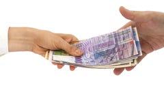 Hands giving money International currencies away Stock Image