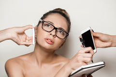 Hands giving phones to young beautiful naked businesswoman holding notebook. Royalty Free Stock Photo
