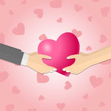 Hands giving a pink heart Stock Photo