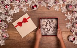 Hands giving or receiving christmas present - in seasonal decora Royalty Free Stock Photo