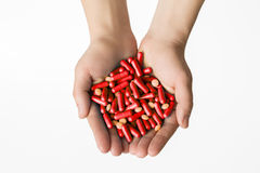 Hands is giving red capsules and orange pills on white background. Royalty Free Stock Photography