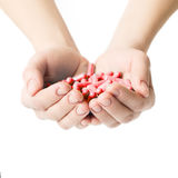 Hands is giving red capsules and orange pills on white background. Royalty Free Stock Photos