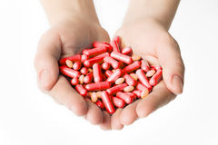 Hands is giving red capsules and orange pills on white background. Stock Image