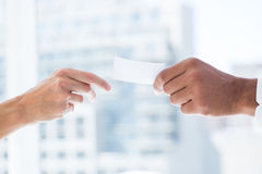 Hands giving small paper sheet to another one. Close up view of hands giving small paper sheet to another one Stock Photography