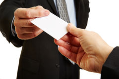 Hands giving and taking business card. Hands of two businesspeople giving and taking an empty business card Stock Photos