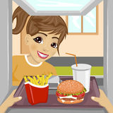 Hands giving tray with fast food meals through a drive-thru window to happy teenager girl Royalty Free Stock Photos