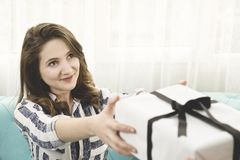 Hands giving young woman surprise gift box. stock photos